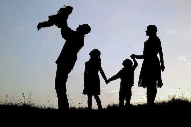 自然の中で子供たちと幸せな家族のシルエット