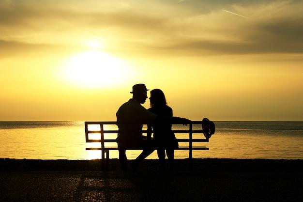 벤치에 해변에서 석양에 행복 한 사랑의 커플의 실루엣