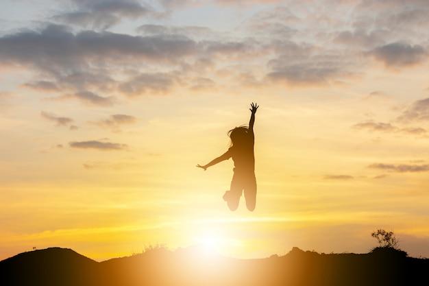Силуэт счастливой молодой женщины скача на концепцию захода солнца, свободы и наслаждения.