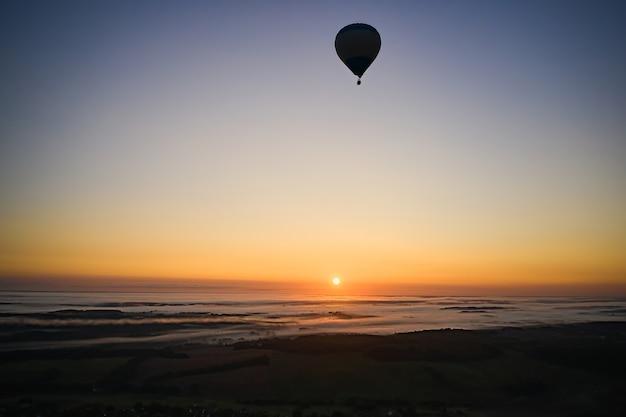 안개와 함께 일출 푸른 하늘 배경에 뜨거운 공기 풍선의 실루엣