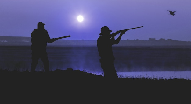 朝の赤い夜明けを背景にハンターのシルエット。銃を持って準備ができて立っています。