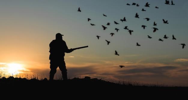 太陽に対して銃を持ったハンターのシルエット、アヒルの待ち伏せ。