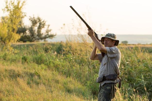 太陽に対して葦に銃を持ったハンターのシルエット、犬とアヒルの待ち伏せ