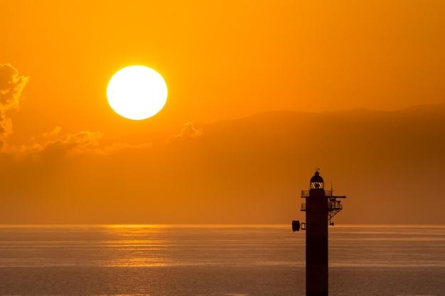 日の出の太陽と灯台のシルエット