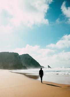 겨울에 해변에서 외로운 남자의 실루엣. 자기 격리 개념입니다. 정신 건강 개념, 의식, 자연과 연결됩니다.