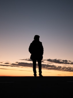 夕日の美しい景色を楽しむ孤独な人のシルエット