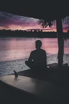 夕日の美しい景色を楽しむ海のそばに座っている孤独な人のシルエット