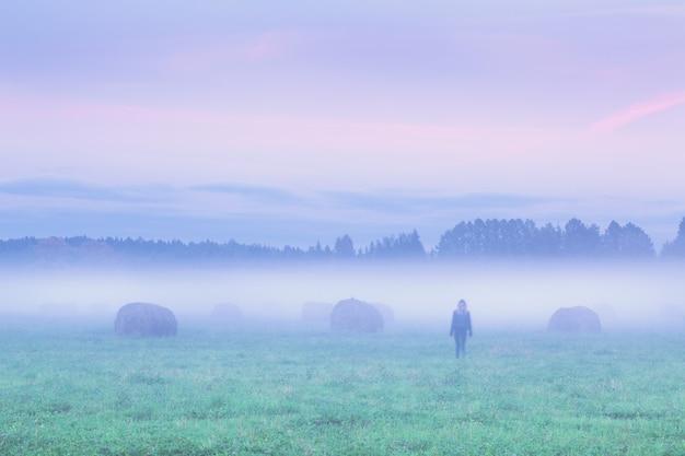 夕暮れ時の干し草の山と霧のフィールドを離れて歩いている孤独な女性のシルエット
