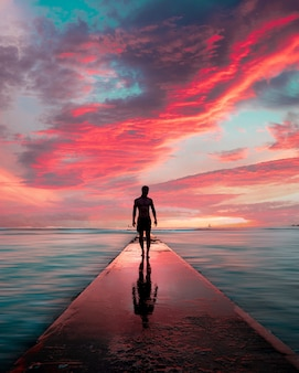彼の反射と美しい息をのむような雲と石の桟橋を歩く男性のシルエット