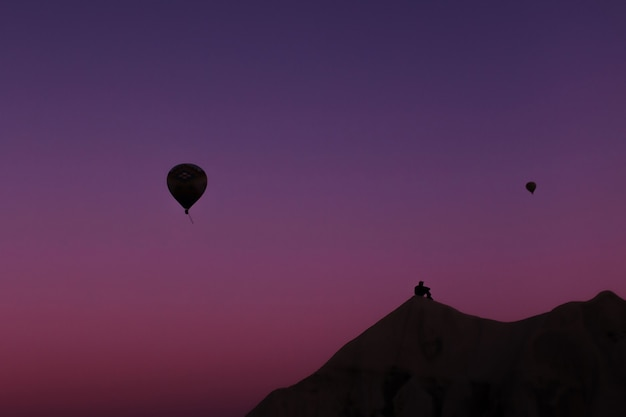 Силуэт человека и красивые воздушные шары на рассвете в каппадокии
