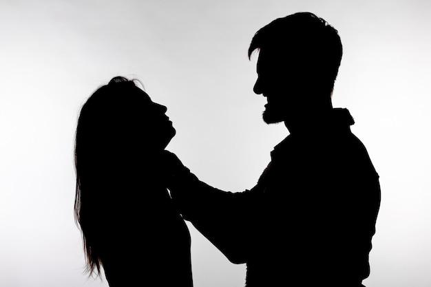 여자를 질식하는 남자의 실루엣.