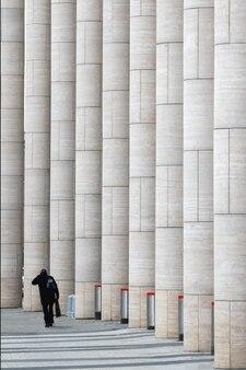 現代のビジネスセンターの大理石の縦の柱にいる男のシルエット。