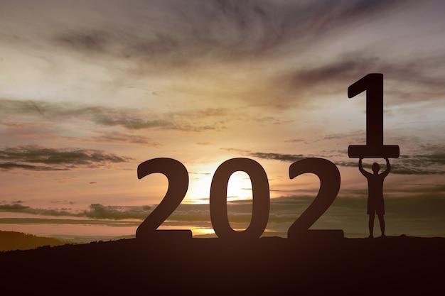새 해를 축 하하는 남자의 실루엣입니다. 2021 년 새해 복 많이 받으세요