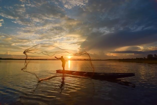 川で伝統的なタイの伝統的な釣りをしている男のシルエット。タイ、チェンマイにて2021年12月5日