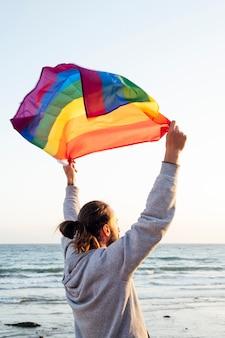 황금빛 햇살이 내리쬐는 열대 해변에서 바람에 날리는 게이 프라이드 무지개 깃발을 들고 있는 남자의 실루엣