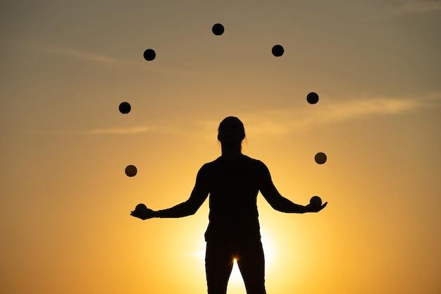 일몰 공으로 저글링하는 남자의 실루엣. 프리미엄 사진