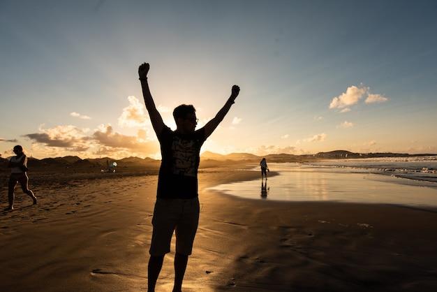 勝利で腕を上げるビーチで男のシルエットついに夏休み