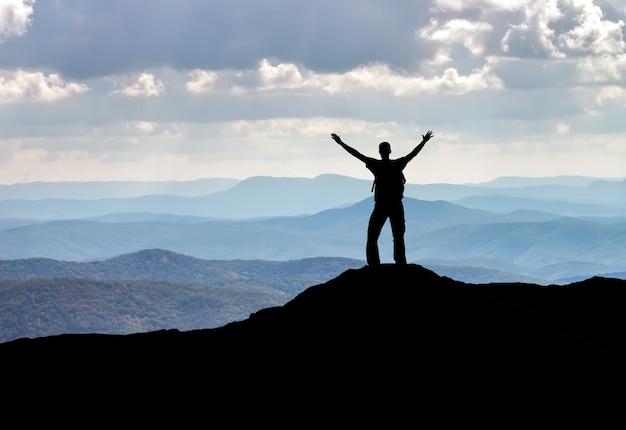 Силуэт человека на вершине горы. человек на скале. концепция спорта и активной жизни