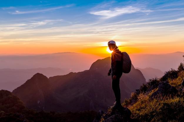 Силуэт человека на вершине горы. человек силуэт на скале.