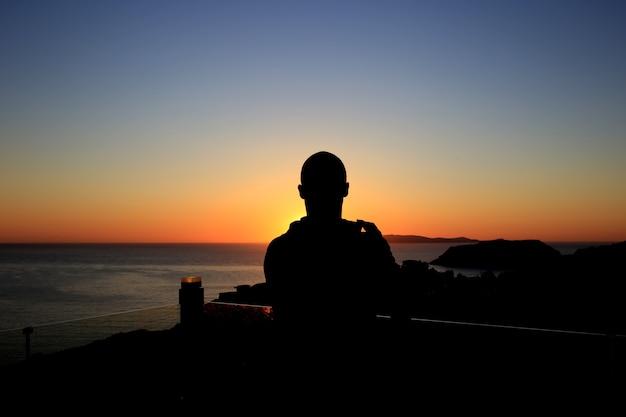 日没または日の出の背景に男のシルエット