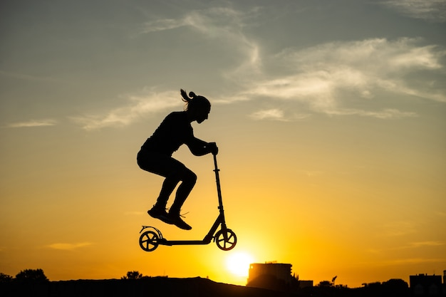 아름다운 일출과 함께 킥 스쿠터를 타고 점프하는 남자의 실루엣