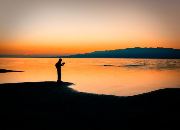 해안선과 바다 위의 일몰 하늘에 서 있는 남자의 실루엣