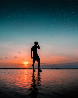 素晴らしい夕日とビーチで水の上に立っている男のシルエット