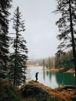 안개가 자욱한 날씨 동안 호수 근처의 숲에서 산책하는 남자의 실루엣