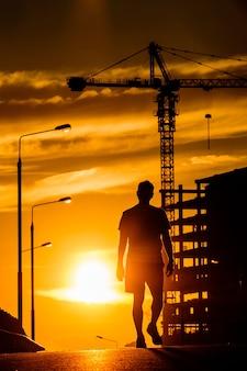 日没時に橋の上を歩く男のシルエット。