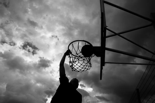 Силуэт человека, который бросает мяч в баскетбольное кольцо на улице на фоне неба с облаками в черно-белом цвете