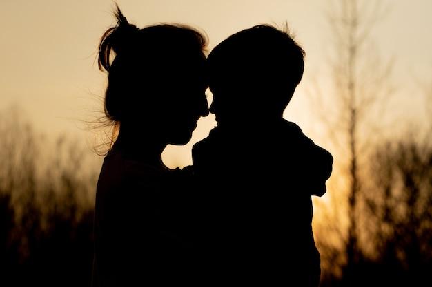 Силуэт матери и сына, играя на открытом воздухе на закате. день матери