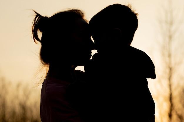 母と息子の日没で野外で遊ぶのシルエット