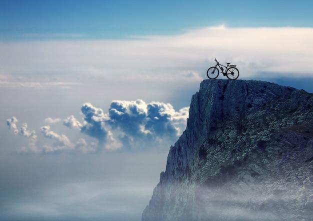 岩の上にあるマウンテンバイクのシルエット