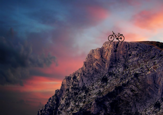 日没時の山のマウンテンバイクのシルエット