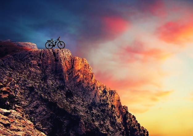 해질녘 바위에 산악 자전거의 실루엣