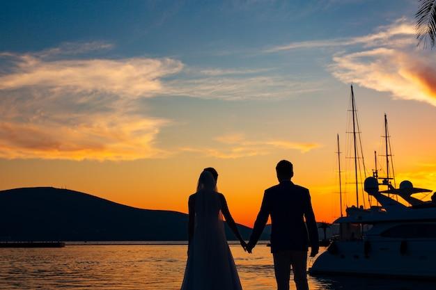モンテネグロの海に沈む夕日を背景にした新婚夫婦のシルエット。