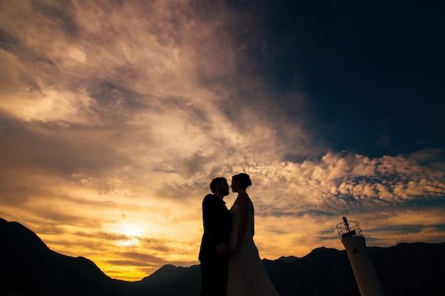 夕日を背景に新婚カップルのシルエット