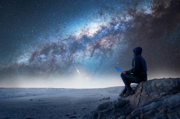 天の川を見つめているラップトップで山の頂上に座っている人のシルエット