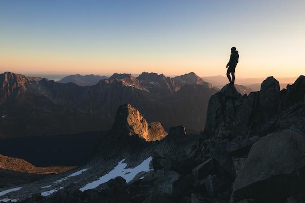 아침에 아름 다운 화려한 하늘 아래 언덕 꼭대기에 서있는 사람의 실루엣