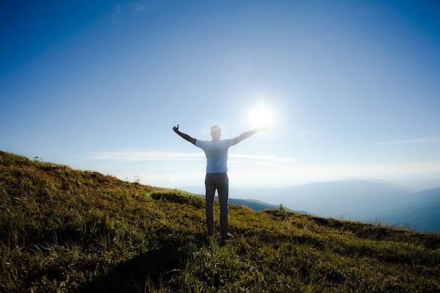 山の頂上に日没時に挙手した人のシルエット