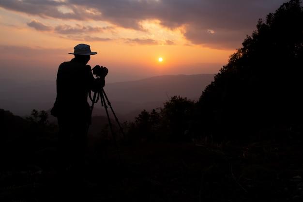Силуэт фотографа, который снимает закат в горах
