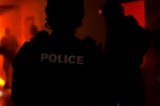 警察官のシルエット。警察の部隊が行動し、建物内で犯人を逮捕