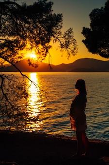 海に沈む夕日の妊婦のシルエット