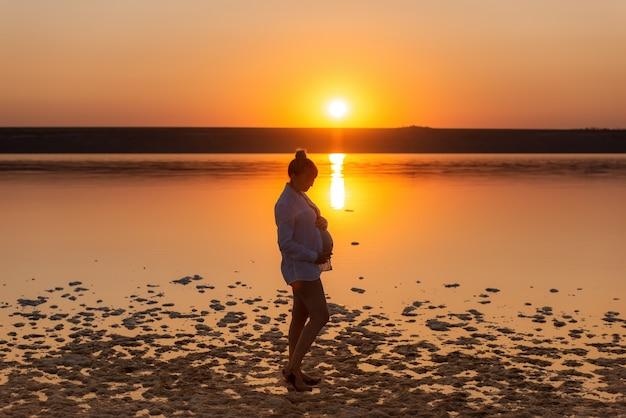 해질녘 해변에 임신 한 여자의 실루엣. 물 배경 임신 한 여자
