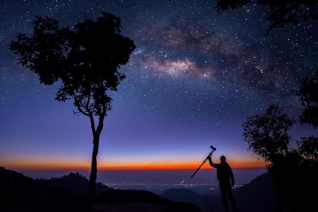 Силуэт профессионального фотографа, снимающего млечный путь на горе