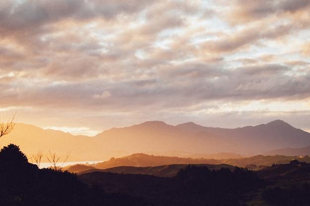 息をのむような夕焼け空の下で美しい山々の範囲のシルエット
