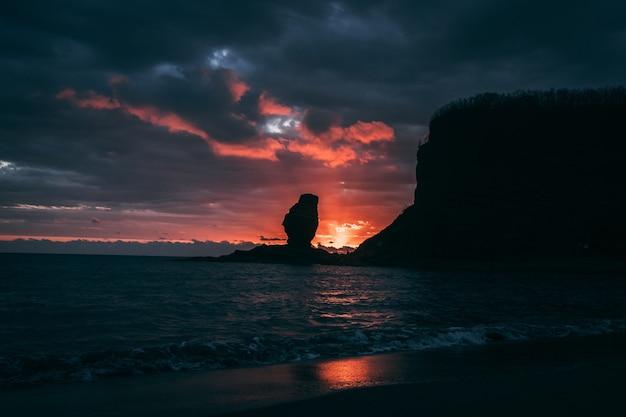 ニューカレドニアのカラフルな夕日に対する海食柱のシルエット