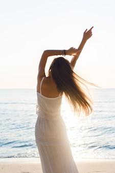 Силуэт худенькой девушки, стоящей на пляже с заходящим солнцем. она носит белое платье. у нее длинные волосы, которые развеваются в воздухе. ее руки вытянулись в воздух