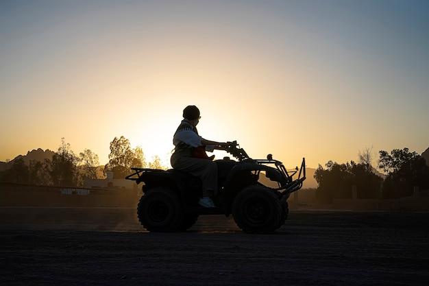 観光客の女性のシルエットは、明るい夕日を背景にクワッドバイクに乗る。エジプトの砂漠での夜の極端な娯楽。