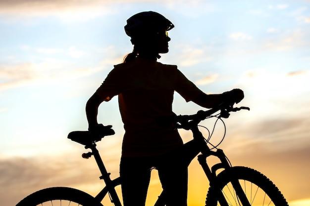 일몰 하늘 배경에 자전거와 여자 사이클의 실루엣. 건강한 라이프 스타일과 스포츠. 여가와 취미